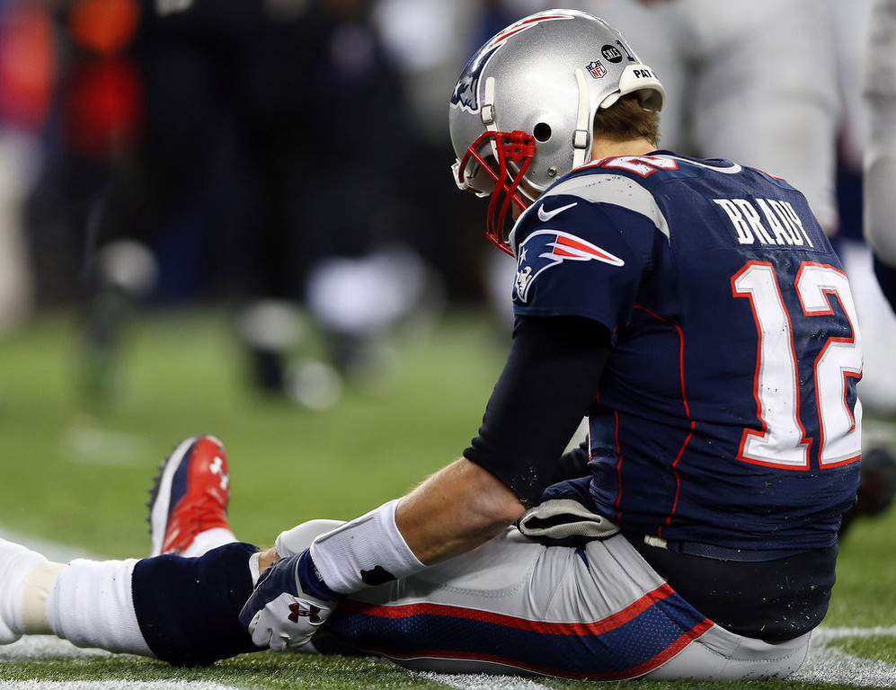 Description of . Tom Brady #12 of the New England Patriots sits on the ground after getting knocked down in the fourth quarter against the Baltimore Ravens during the 2013 AFC Championship game at Gillette Stadium on January 20, 2013 in Foxboro, Massachusetts.  (Photo by Elsa/Getty Images)