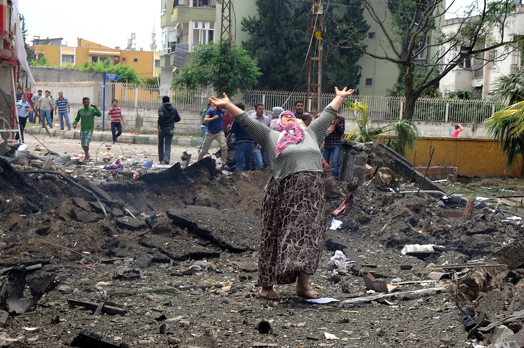 Description of . A woman raises her arms and shouts as she stands on the site where car bombs exploded on May 11, 2013 near the town hall in Reyhanli, just a few kilometres from the main border crossing into Syria, killing four people and wounded another 18, according to an initial toll.  CEM GENCO/AFP/Getty Images