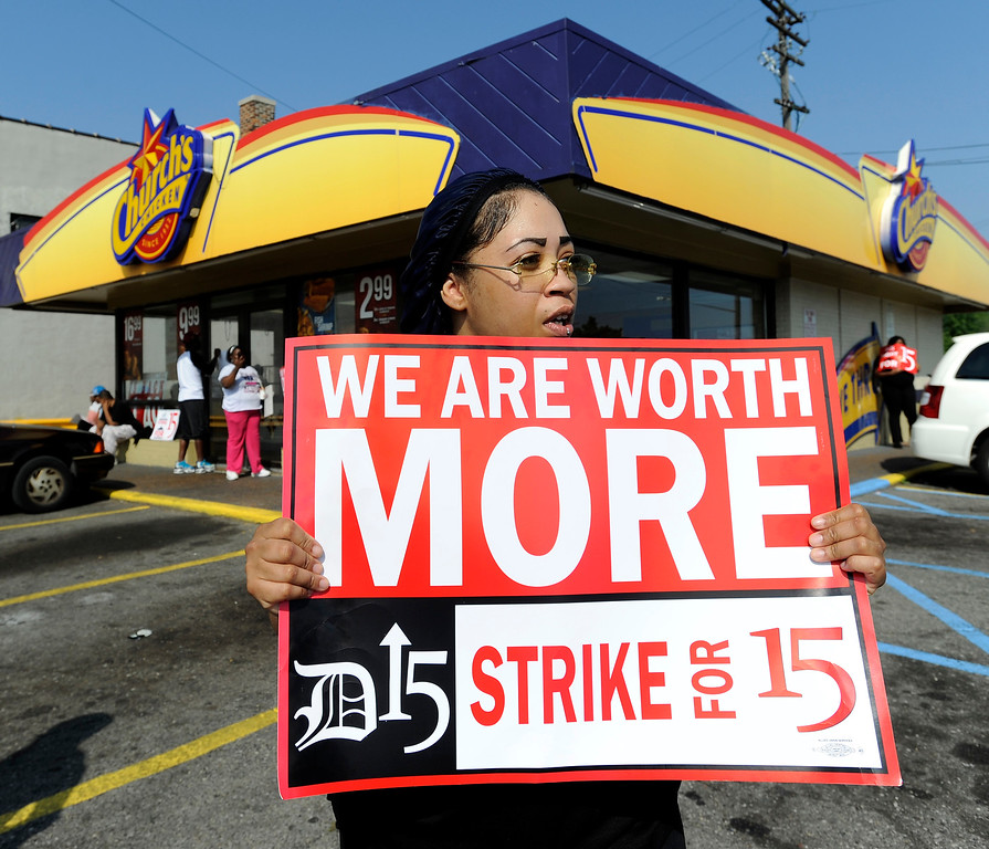 Description of . Taco Bell employee Shanise Stitt pickets with other protestors in front of the Church's Chicken fast food restaurant in Detroit on Thursday, Aug. 29, 2013.  (AP Photo/Detroit News, David Coates)