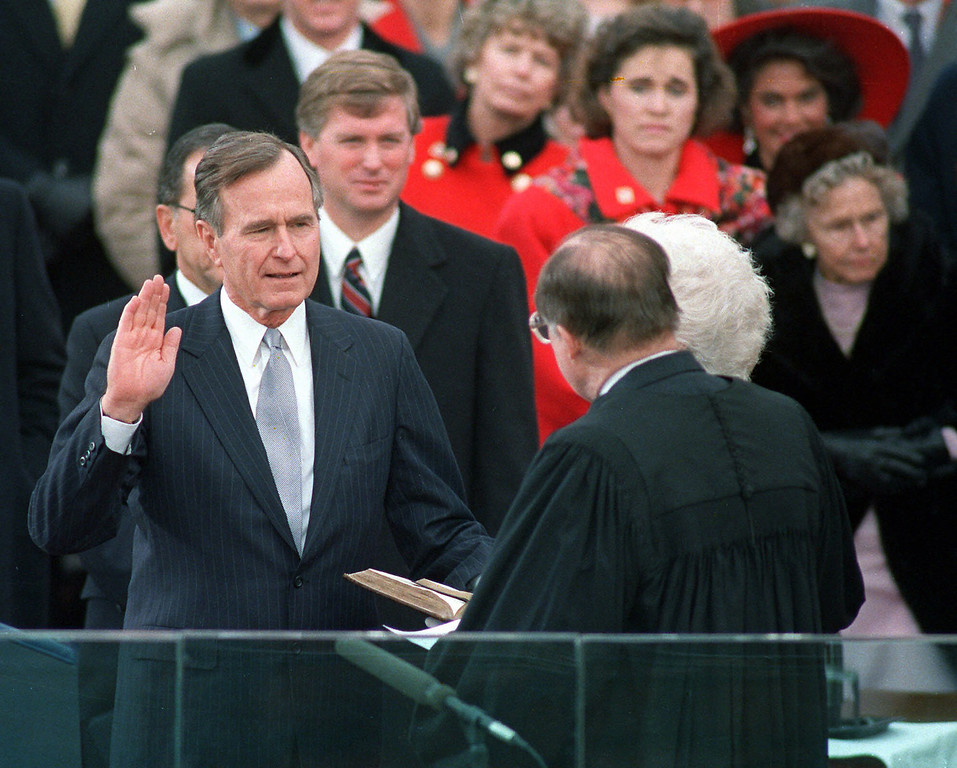 Description of . President George Bush raises his hand on Jan. 20,1989 as he takes the oath of office as president of the United States outside the Capitol. Vice President Dan Quayle watches from behind. (AP Photo/Ron Edmonds)