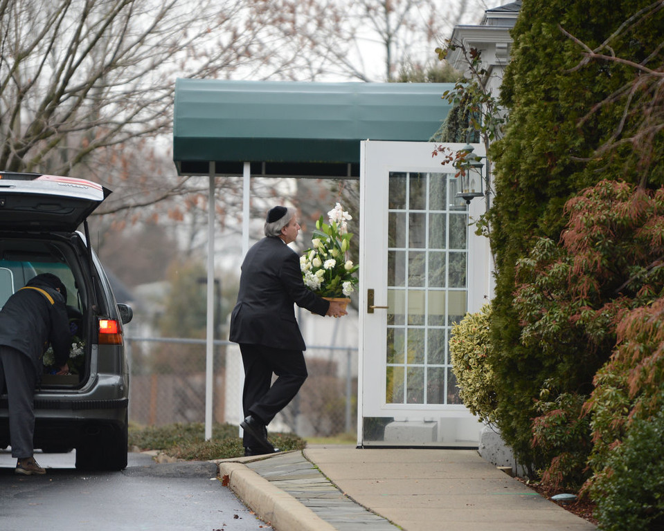 Description of . A man arrives with flowers at Abraham L. Green and Son Funeral Home in Fairfield, Connecticut, December 17, 2012 for Noah Pozner,6 one of the victims of the elementary school shooting in Newtown, Connecticut.  Funerals began Monday after the school massacre that took the lives of 20 small children and six staff, triggering new momentum for a change to America's gun culture. The first burials, held under raw, wet skies, were for two six-year-old boys who were among those shot in Sandy Hook Elementary School. On Tuesday, the first of the girls, also aged six, was due to be laid to rest. There were no Monday classes at all across Newtown, and the blood-soaked elementary school was to remain a closed crime scene indefinitely, authorities said.    AFP PHOTO/Don EMMERT/AFP/Getty Images
