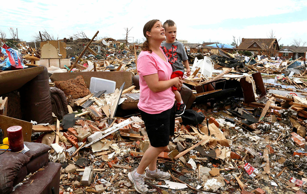 Description of . Tracy Stephan, holding her son Timothy, 3, looks at her tornado-destroyed home on 6th Avenue in Moore, Oklahoma May 23, 2013. The tornado was the strongest in the United States in nearly two years and cut a path of destruction 17 miles long and 1.3 miles wide. REUTERS/Rick Wilking