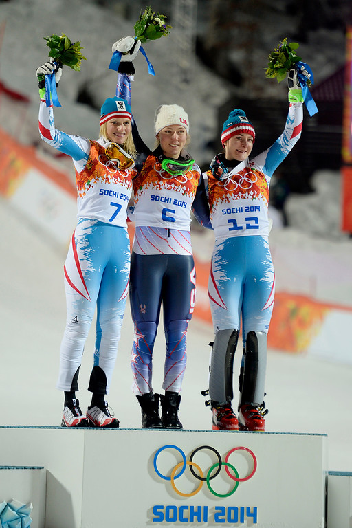 Description of . Gold medalist American Mikaela Shiffrin raises her hands as she is announced while silver medalist Marlies Schild (left) and bronze medalist Kathrin Zettel (both of Austria) join after ladies' slalom run 2. Sochi 2014 Winter Olympics on Friday, February 21, 2014 at Rosa Khutor Alpine Center. (Photo by AAron Ontiveroz/ The Denver Post)