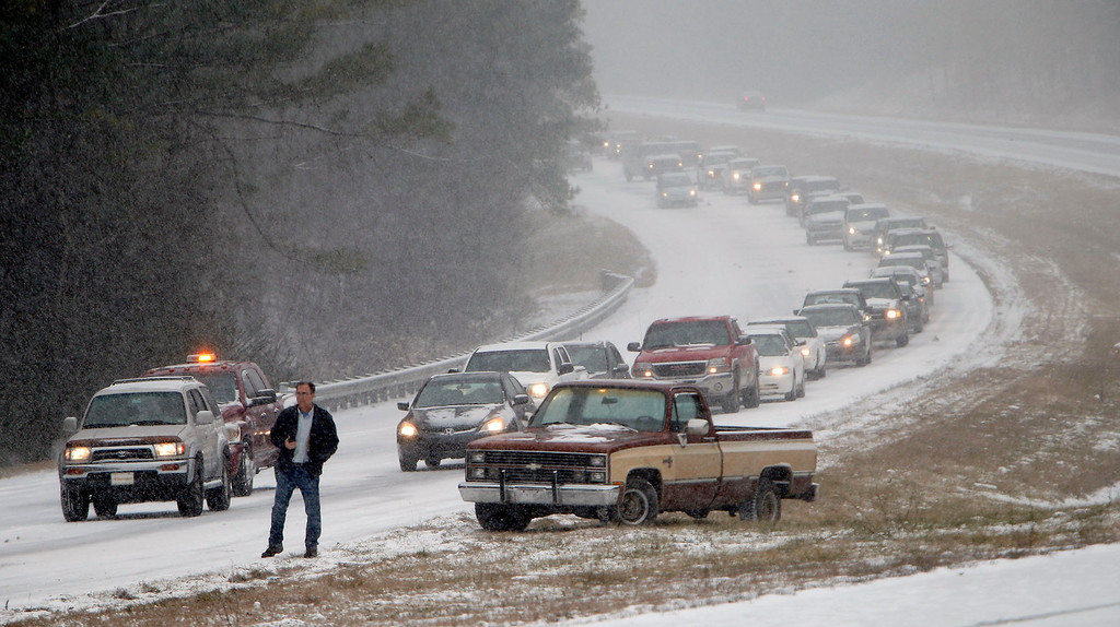 Description of . Vehicles are backed up on a snow covered US Highway 280 during a snow storm, Tuesday, Jan. 28,  2014 in Chelsea, Ala.   (AP Photo/Hal Yeager)