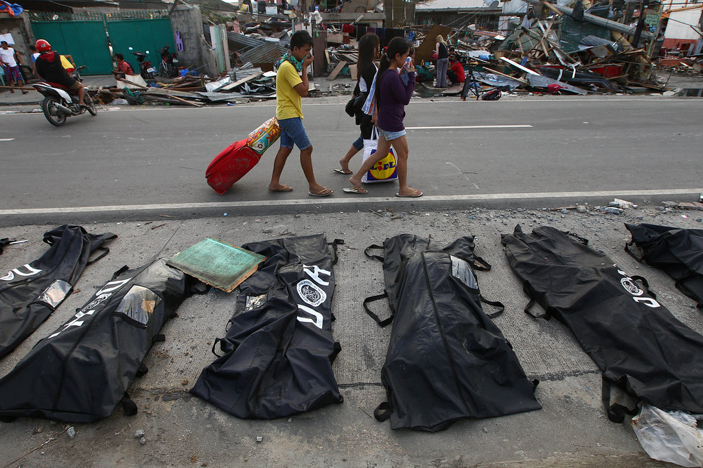 Description of . People cover their noses from the stench of dead bodies in an area affected by Typhoon Haiyan in Tacloban, Philippines, Wednesday, Nov. 13, 2013. Typhoon Haiyan, one of the strongest storms on record, slammed into six central Philippine islands on Friday, leaving a wide swath of destruction. (AP Photo/Dita Alangkara)