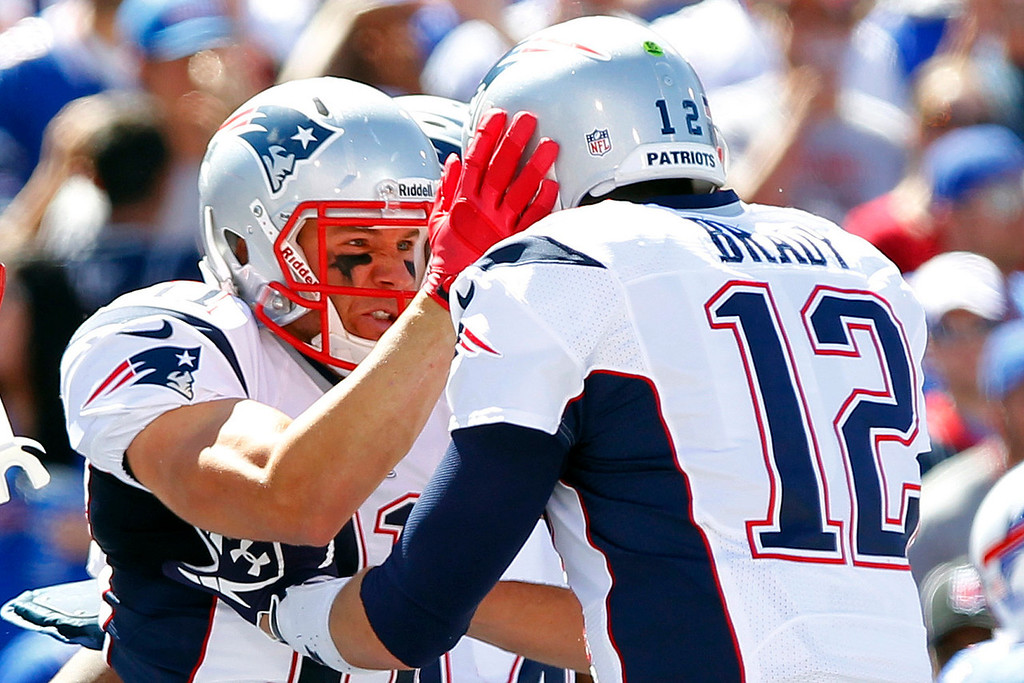Description of . New England Patriots' Julian Edelman, left, celebrates with teammate Tom Brady, right, after catching a touchdown pass during the first half of an NFL football game against the Buffalo Bills, Sunday, Sept. 8, 2013, in Orchard Park. (AP Photo/Bill Wippert)