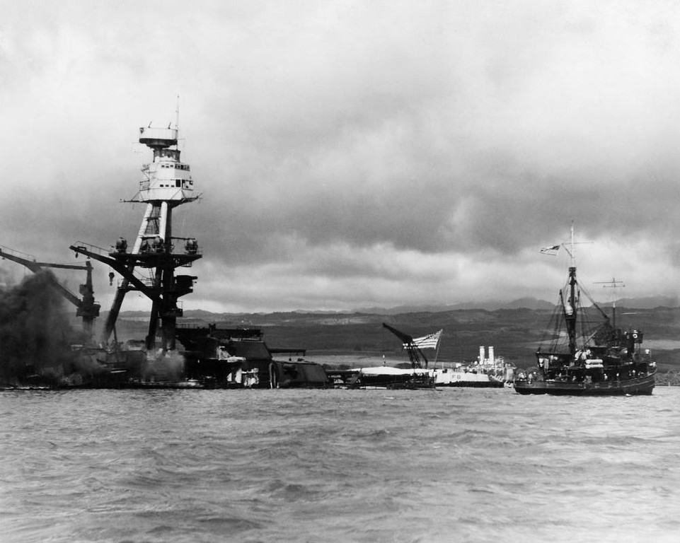 Description of . Battle ship Arizona at pearl Harbor, December 1941. The photo was taken shortly after the battleship was bombed and destroyed during the surprise attack by Japanese forces, December 7, 1941. The vessel at right is a rescue tug. Flag still flying the ship is resting on the bottom of the ocean with decks flooded. (AP Photo)