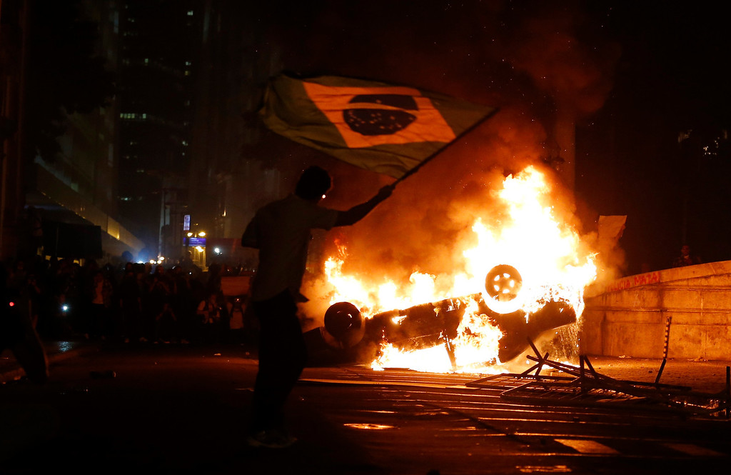 Description of . A demonstrator waves a Brazilian flag by a burning a car in downtown Rio de Janeiro June 17, 2013.Tens of thousands of demonstrators marched through the streets of Brazil's biggest cities on Monday in a growing protest that is tapping into widespread anger at poor public services, police violence and government corruption.    REUTERS/Sergio Moraes