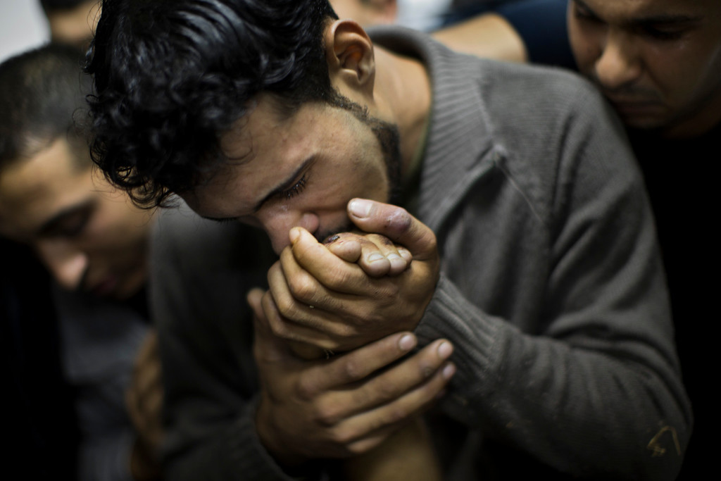 Description of . In this Nov. 18, 2012 file photo, a Palestinian man kisses the hand of a dead relative in the morgue of Shifa Hospital in Gaza City.  (AP Photo/Bernat Armangue, File)