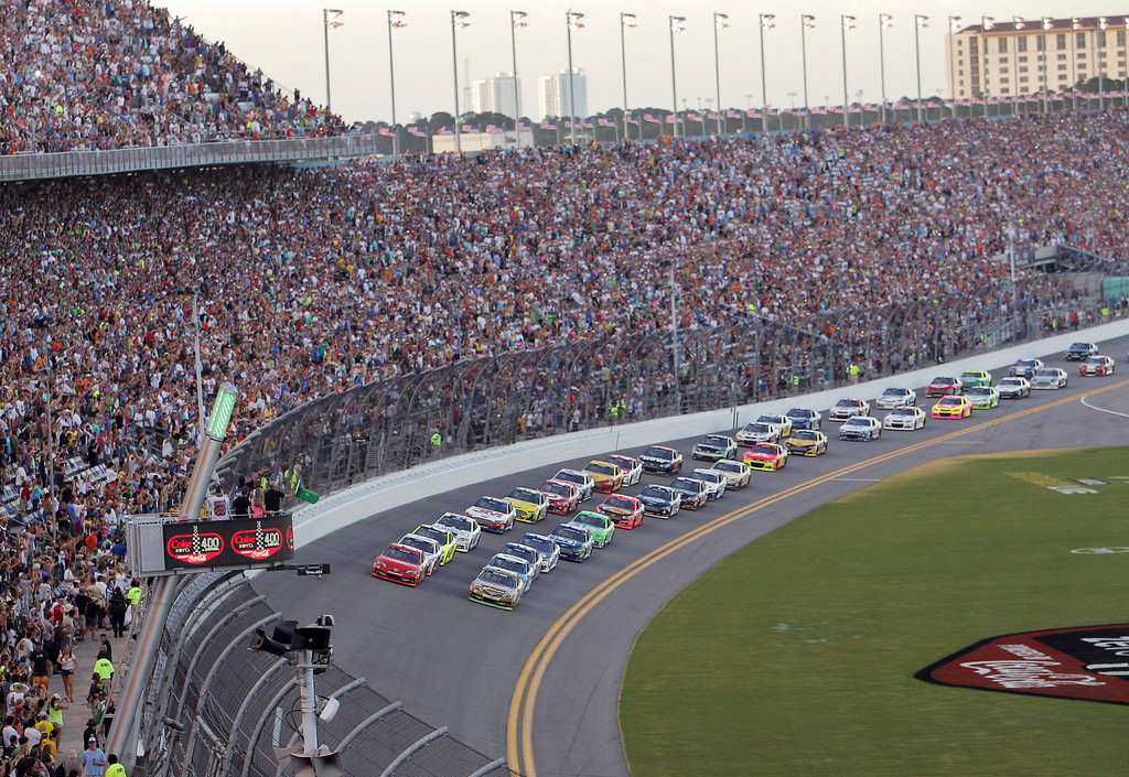 Description of . Kyle Busch, front right, and Matt Kenseth front left, lead the the field of cars to start the NASCAR Sprint Cup auto race at Daytona International Speedway, Saturday, July 6, 2013, in Daytona Beach, Fla. (AP Photo/David Graham)
