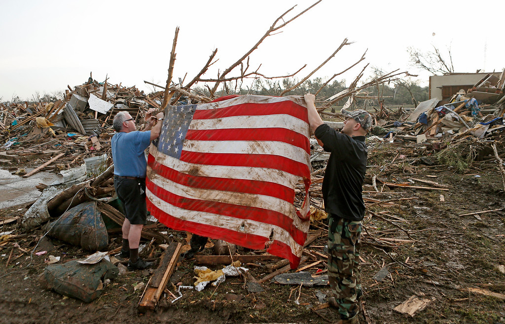 . Clark Gardner, at left, and another man place an American flag on debris in a neighborhood off of Telephone Road in Moore, Okla., after a tornado moved through the area on Monday, May 20, 2013. (AP Photo/ The Oklahoman, Bryan Terry)