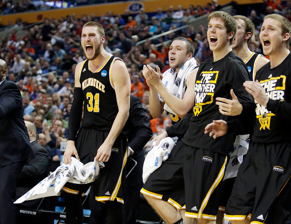 Description of . Milwaukee's Matt Tiby (31) joins teammates in cheering during first half of a second-round game against Villanova in the NCAA college basketball tournament in Buffalo, N.Y., Thursday, March 20, 2014. (AP Photo/Nick LoVerde)