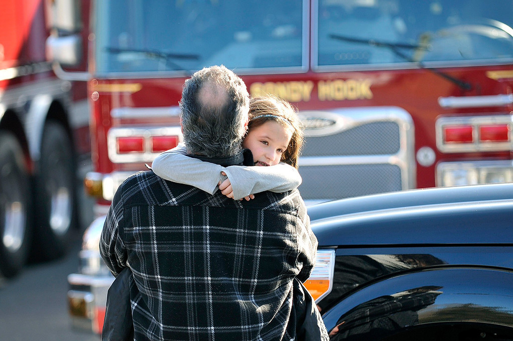 Description of . People leave the scene of a shooting incident at Sandy Hook Elementary School in Newtown, Connecticut, in this December 14, 2012 handout photo. Twenty-six people, including 20 children, have been killed in a shooting at Sandy Hook Elementary School in Newtown, Connecticut.  REUTERS/John Woike/Hartford Courant/Handout