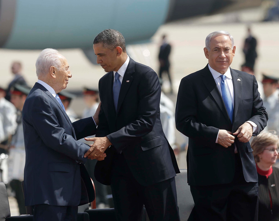 Description of . President Barack Obama, center, shakes hands with Israeli President Shimon Peres , left, while on stage with Israeli Prime Minister Benjamin Netanyahu, right, during his arrival ceremony at Ben Gurion International Airport in Tel Aviv, Israel, Wednesday, March 20, 2013, (AP Photo/Pablo Martinez Monsivais)