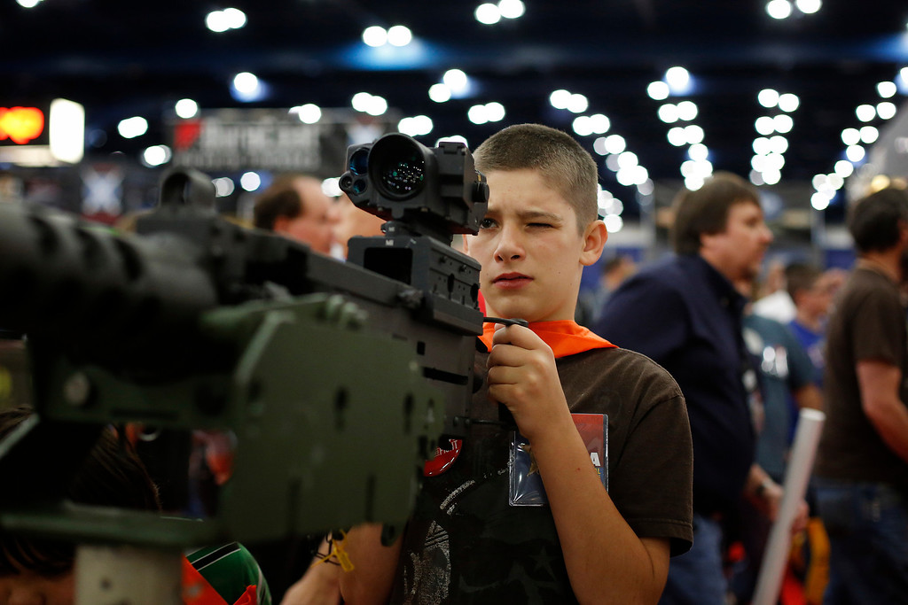 Description of . 13-year-old Jacob La looks down the sight of a mounted machine gun, during the NRA Annual Meeting of Members at the National Rifle Association's 142 Annual Meetings and Exhibits in the George R. Brown Convention Center Saturday, May 4, 2013, in Houston. National Rifle Association leaders told members Saturday that the fight against gun control legislation is far from over, with battles yet to come in Congress and next year's midterm elections, but they vowed that none in the organization will ever have to surrender their weapons. (AP Photo/Houston Chronicle, Todd Spoth)