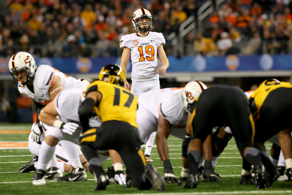 Description of . ARLINGTON, TX - JANUARY 03:  Kicker Ben Grogan #19 of the Oklahoma State Cowboys looks up before he kicks against the Missouri Tigers in the first half during the AT&T Cotton Bowl on January 3, 2014 in Arlington, Texas.  (Photo by Ronald Martinez/Getty Images)