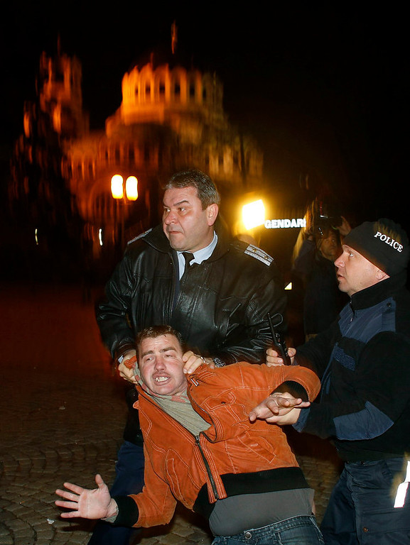 Description of . Bulgarian police detain a man during a protest against high electricity prices, in front of the parliament in Sofia on February 18, 2013. Bulgaria's government sacked Finance Minister Simeon Djankov on Monday, dumping the man who has kept a tight rein on spending in the EU's poorest member amid nationwide protests over electricity prices. The sacking did little to soothe protesters' anger and several thousand people gathered around the country to continue Bulgaria's biggest demonstrations since 1997, when a banking crisis and hyperinflation caused national unrest.  REUTERS/Stoyan Nenov
