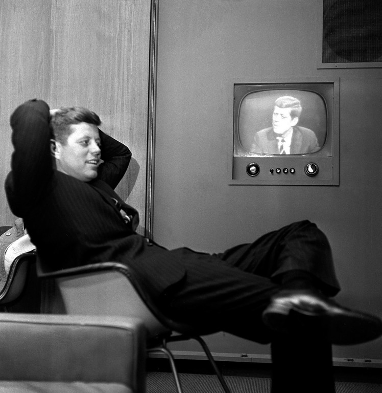 Description of . Sen. Kennedy sits next to a playback of his televised appearance in Milwaukee, Wis., for the Wisconsin presidential primary two days later om 1960. Associated Press file