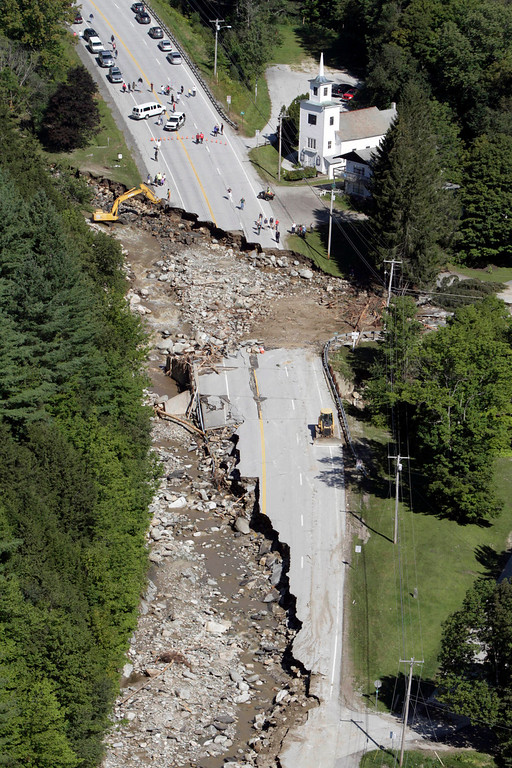 Description of . This Aug. 30, 2011 file aerial photograph shows destruction of Route 4 in Killington, Vt., after Tropical Storm Irene passed through New England. Global warming is rapidly turning America into a stormy and dangerous place, with rising seas and disasters upending lives from flood-stricken Florida to the wildfire-ravaged West, according to a new U.S. federal scientific report released Tuesday, May 6, 2014.   (AP Photo/Toby Talbot, File)