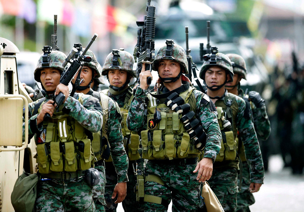 Description of . Fresh troops arrive to reinforce other government troopers as they continue their assault on Muslim rebels holding scores of hostages Thursday, Sept. 12, 2013, in Zamboanga city in the southern Philippines.  (AP Photo/Bullit Marquez)