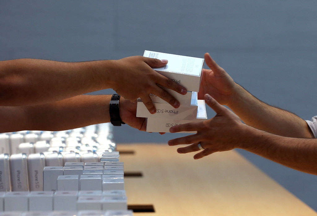 Description of . Apple Store employees pass boxes of the new Apple iPhone 5S on September 20, 2013 in Palo Alto, California.  (Photo by Justin Sullivan/Getty Images)
