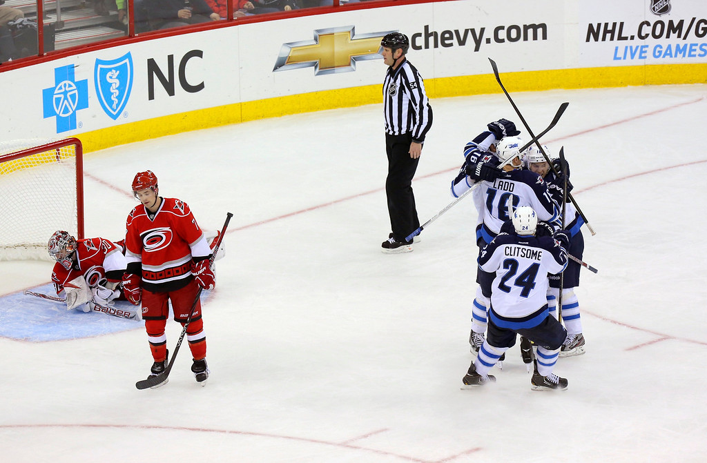 . The Winnipeg Jets\' Andrew Ladd (16) is congratulated for his goal by teammates Grant Clitsome (24), Blake Wheeler (not seen) and Bryan Little (18) near the Carolina Hurricanes\' Cam Ward (ground L) and Ryan Murphy during the third period of their NHL hockey game in Raleigh, North Carolina February 21, 2013. The Jets won 4-3.  REUTERS/Ted Richardson