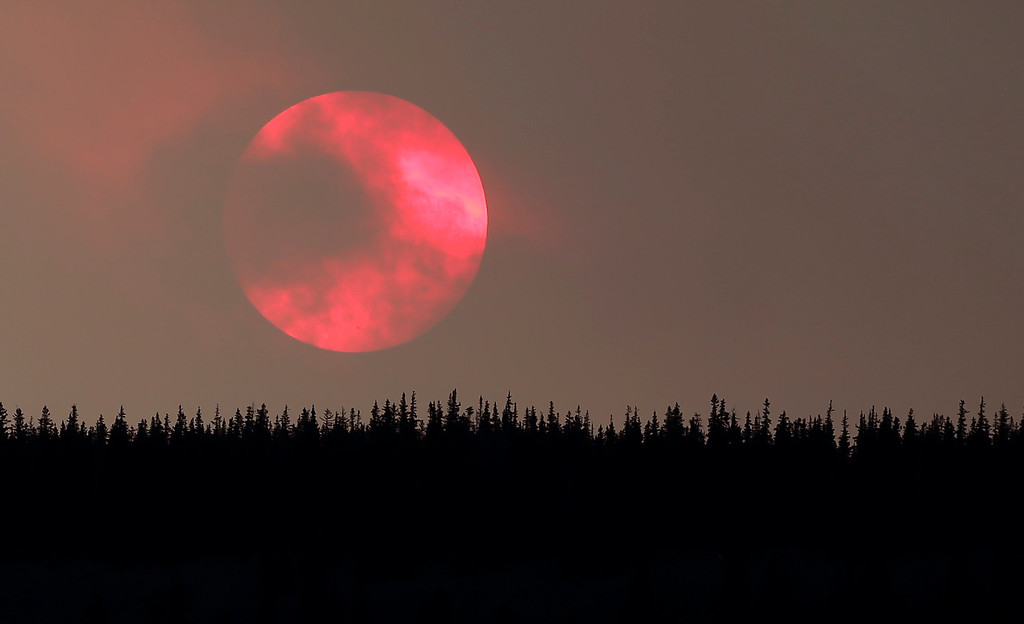 Description of . Wildfire smoke masks the sun as it sets over a ridge Saturday, June 22, 2013, near South Fork, Colo.   (AP Photo/Gregory Bull)