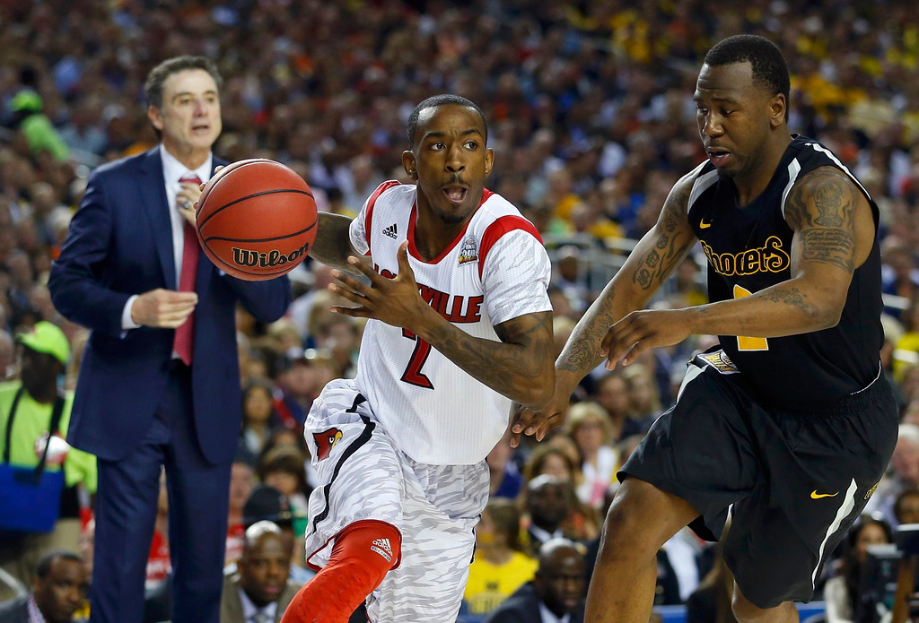 Description of . Louisville Cardinals guard Russ Smith (L) drives to the net on Wichita State Shockers guard Malcolm Armstead during the second half of their NCAA men's Final Four basketball game in Atlanta, Georgia April 6, 2013.  REUTERS/Chris Keane