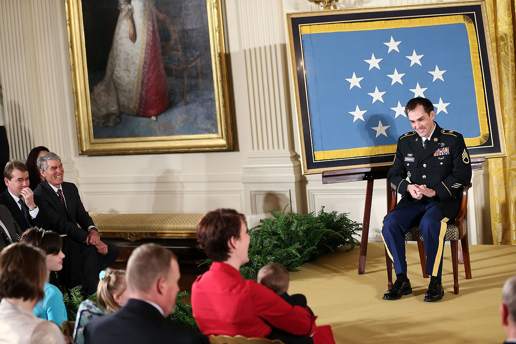 Description of . Clinton Romesha (R), a former active duty Army Staff Sergeant, sits during the presentation of his Medal of Honor for conspicuous gallantry by U.S. President Barack Obama at the White House February 11, 2013 in Washington, DC. (Photo by Alex Wong/Getty Images)