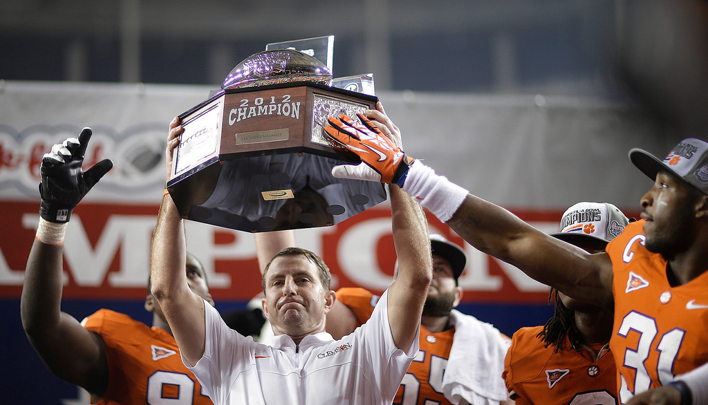 Description of . Clemson coach Dabo Swinney holds the trophy after Clemson defeated LSU 25-24 in the Chick-fil-A Bowl NCAA college football game, Monday, Dec. 31, 2012, in Atlanta. (AP Photo/David Goldman)