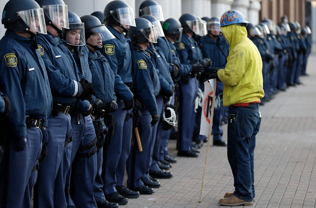 . Protester Blake Nance, of Detroit, stands by a line of Michigan State Police guarding the George W. Romney State Building, where Gov. Snyder has an office in Lansing, Mich., Tuesday, Dec. 11, 2012. The crowd is protesting right-to-work legislation passed last week. Michigan could become the 24th state with a right-to-work law next week. Rules required a five-day wait before the House and Senate vote on each other\'s bills; lawmakers are scheduled to reconvene Tuesday and Gov. Snyder has pledged to sign the bills into law. (AP Photo/Paul Sancya)