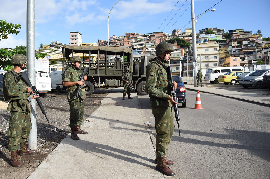 Description of . Brazilian soldiers stand guard during security operations in Vila Pinheiro --part of the Mare shantytown complex near the Galeao (Antonio Carlos Jobim) international airport-- in the north suburb of Rio de Janeiro on April 5, 2014. Thousands of soldiers --including some 2,000 paratroopers, 450 sailors and 200 military police-- in armored vehicles, trucks and on foot entered one of Rio de Janeiro's most notorious slums to provide security less than three months before the World Cup and until July 30. CHRISTOPHE SIMON/AFP/Getty Images