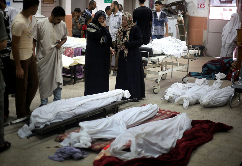 Description of . Palestinian relatives check the bodies of family members, killed the night before in Israeli air strikes, at the Khan Yunis hospital in the southern Gaza Strip on July 29, 2014. The fighting between Israeli troops and Hamas militants raged on unabated with scores more Palestinians killed as the death toll in Gaza rose well over 1,100, most of them civilians.  AFP PHOTO/ BILAL  TELAWI/AFP/Getty Images