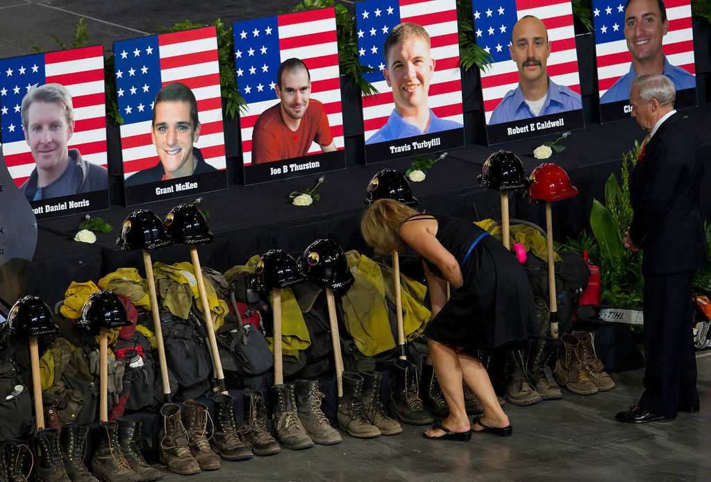 Description of . Photos of some of the 19 fallen firefighters line the front of the stage before a memorial service at Tim's Toyota Center in Prescott Valley, Ariz. on Tuesday, July 9, 2013.   (AP Photo/The Arizona Republic, Michael Chow, Pool)