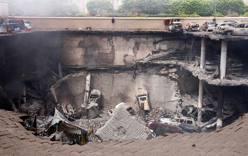 Description of . This photo released by the Kenya Presidency shows the collapsed upper car park of the Westgate Mall in Nairobi, Kenya Thursday, Sept. 26, 2013. Working near bodies crushed by rubble in a bullet-scarred, scorched mall, FBI agents continued fingerprint, DNA and ballistic analysis to help determine the identities and nationalities of victims and al-Shabab gunmen who attacked the shopping center, killing more than 60 people. (AP Photo/Kenya Presidency)