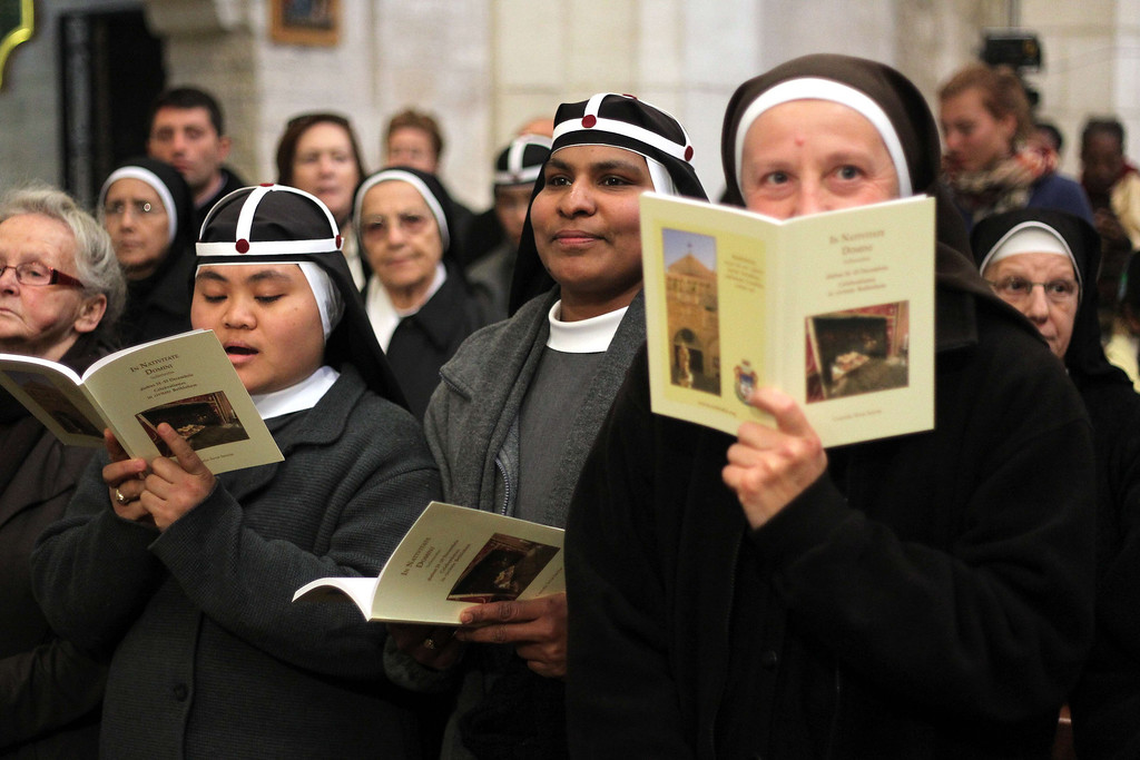 Description of . Nuns follow the service led by the Latin Patriarch of Jerusalem Fuad Twal (unseen), the head of the Roman Catholic Church in the Holy Land, at the Church of the Nativity as Christians gather for Christmas celebrations in the West Bank city of Bethlehem, on December 24, 2013. Thousands of Palestinians and tourists flocked into the West Bank city of Bethlehem to mark Christmas in the