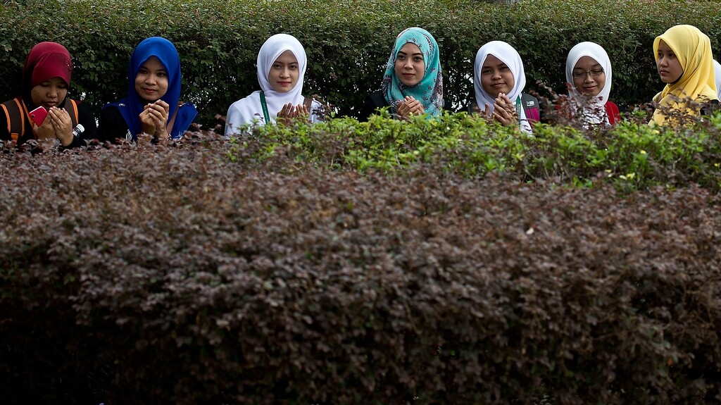 Description of . Young Malaysian Muslim girls offer Friday prayers as they sit outside the Putra mosque in Putrajaya on March 21, 2014. Surveillance aircraft scoured a remote and stormy section of the Indian Ocean on March 20 for a pair of floating objects that Australia and Malaysia guardedly called a