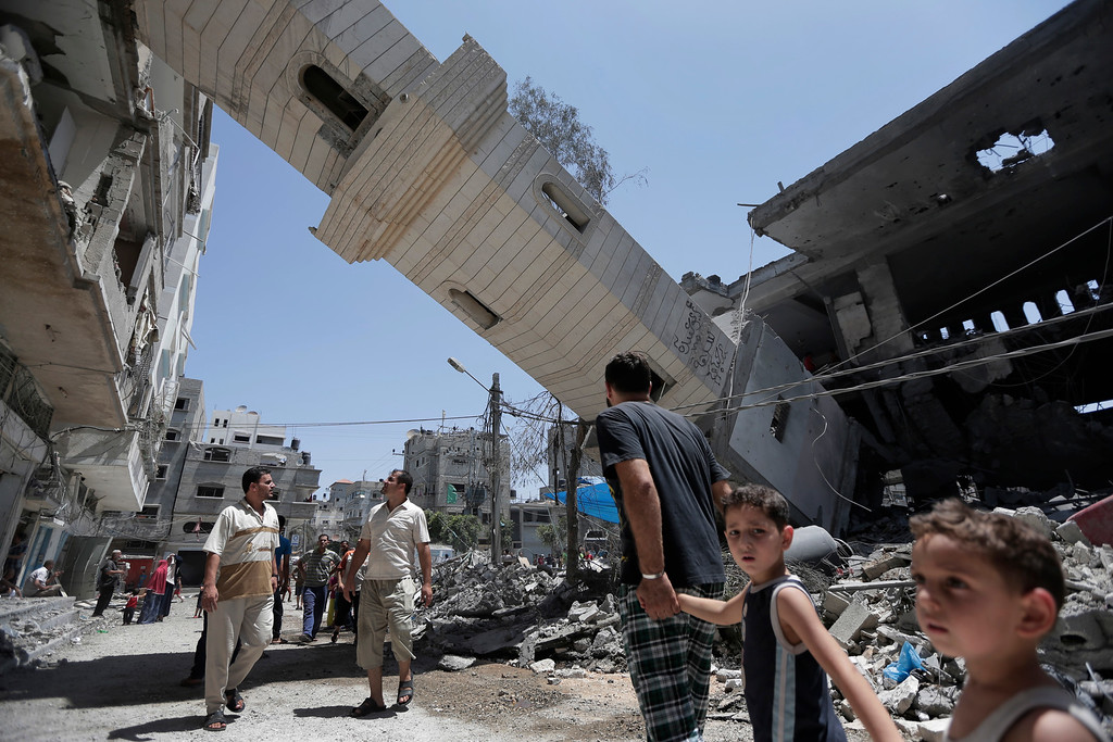 Description of . Palestinians inspect damage to adjacent houses from a fallen minaret of the Al-Sousi mosque that was destroyed in an Israel strike, at the Shati refugee camp, in the northern Gaza Strip, Wednesday, July 30, 2014.  Israeli aircraft struck dozens of Gaza sites on Wednesday, including five mosques it said were being used by militants, while several other areas came under tank fire. (AP Photo/Lefteris Pitarakis)