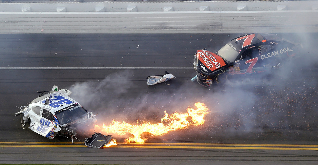 Description of . Kyle Larson, left, slides to a stop near Regan Smith (7) after a wreck at the conclusion of the NASCAR Nationwide Series auto race Saturday, Feb. 23, 2013, at Daytona International Speedway in Daytona Beach, Fla. (AP Photo/Chris O'Meara)