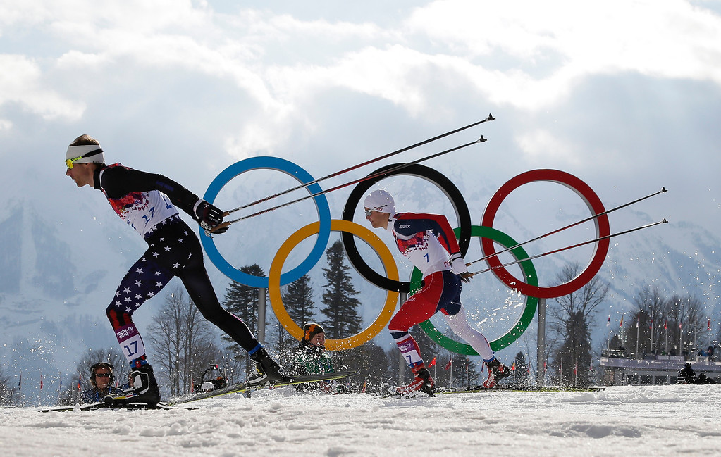 Description of . United States' Andrew Newell leads Norway's Eirik Brandsdal as they ski past the Olympic rings during the men's cross-country sprint quarterfinals, at the 2014 Winter Olympics, Tuesday, Feb. 11, 2014, in Krasnaya Polyana, Russia. (AP Photo/Felipe Dana)