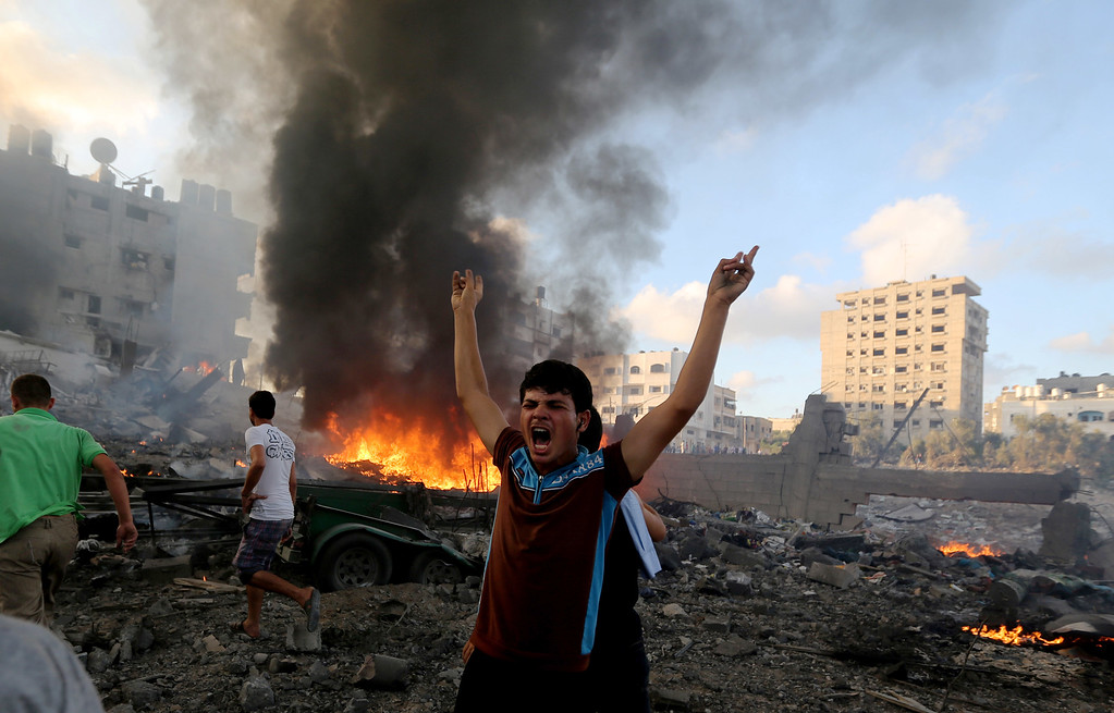 Description of . In this Thursday, July 24, 2014, file photo, a Palestinian shouts in an area damaged in an Israeli airstrike in Gaza City in the Gaza Strip. On Thursday, July 31, 2014, the U.N.'s top human rights official accused both Israel and Hamas of committing war crimes in the current Gaza fighting. (AP Photo/Hatem Moussa, File)
