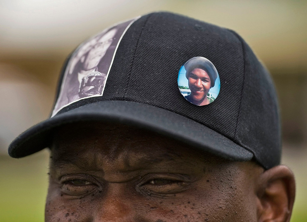 Description of . Randy Casey, of Sanford, wearing a hat with a Malcolm X sticker and Trayvon Martin button, listens to speakers during an open forum to discuss the George Zimmerman second-degree murder trial and verdict at Melon Park in Sanford, Florida, July 14, 2013. U.S. President Barack Obama called for calm on Sunday after the acquittal of Zimmerman in the shooting death of black teenager Trayvon Martin, as civil rights demonstrators planned rallies in a handful of cities to condemn racial profiling. REUTERS/Steve Nesius