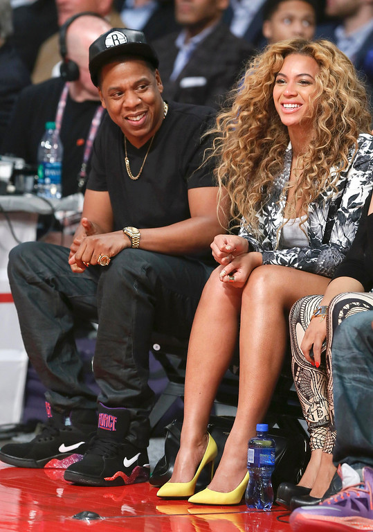 Description of . Singer Beyonce and her husband Jay-Z sit courtside before the NBA All-Star basketball game in Houston, Texas, February 17, 2013.  REUTERS/Lucy Nicholson