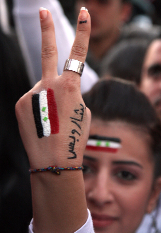 Description of . Pro-Syrian President Bashar Assad protester, flashes V sign as she painted on her hand Syrian flag with Arabic words read: