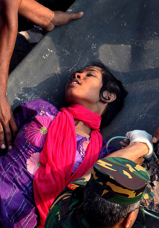 Description of . Survivor Reshma Begum lies on a stretcher after being pulled out from the rubble of a building that collapsed in Savar, near Dhaka, Bangladesh, Friday, May 10, 2013. (AP Photo)