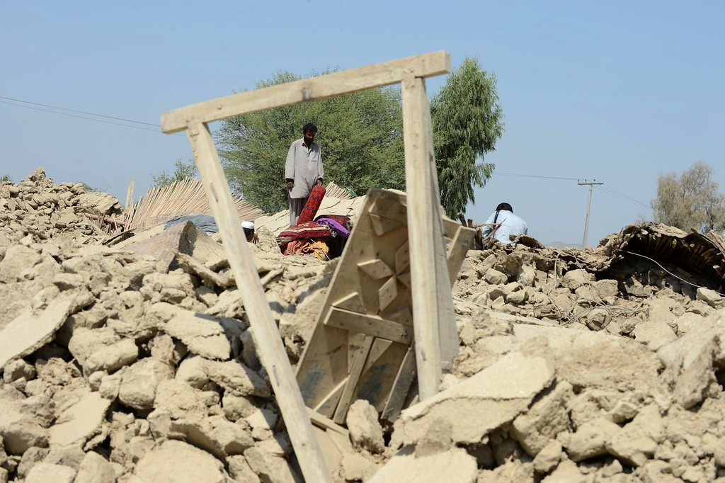 Description of . Pakistani survivors gather around their destroyed houses in the earthquake-devastated district of Awaran on September 25, 2013.    AFP PHOTO/Banaras KHAN/AFP/Getty Images