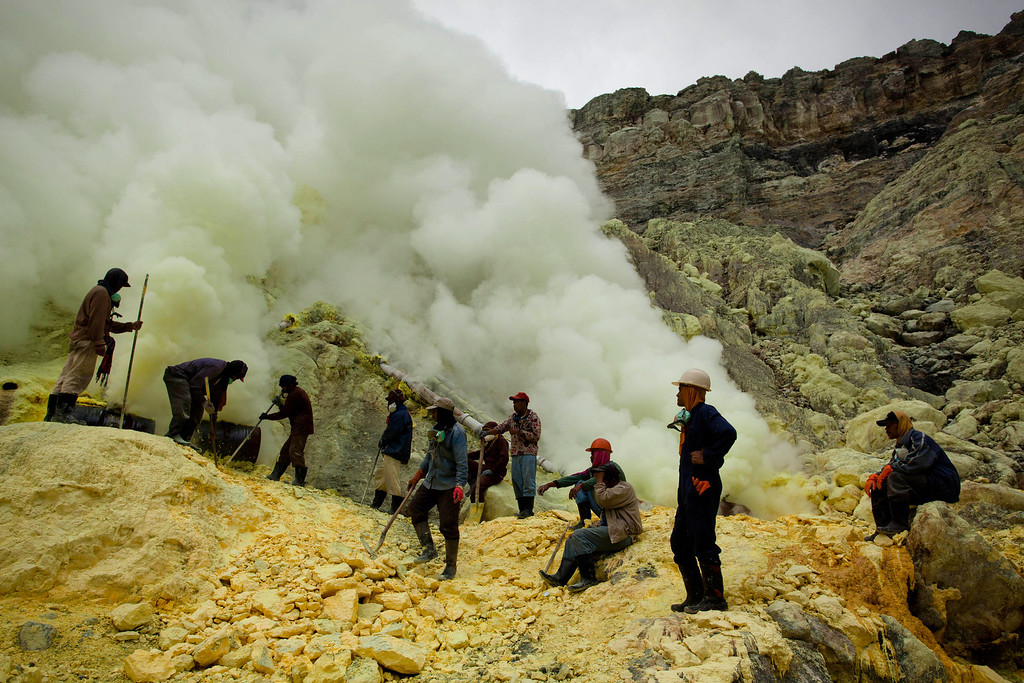 Description of . Miners uses poles to extract sulphur from pipes at the flow crater during an annual offering ceremony on the Ijen volcano on December 17, 2013 in Yogyakarta, Indonesia. (Photo by Ulet Ifansasti/Getty Images)