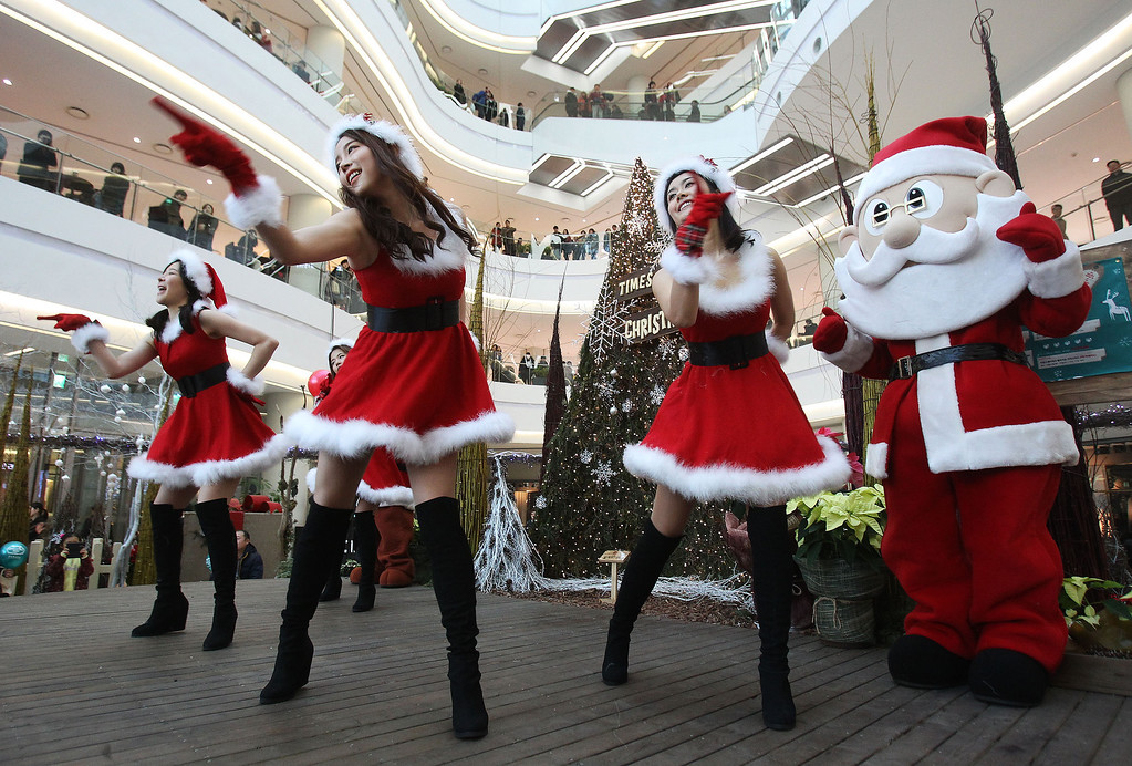 Description of . Employees dressed as Santa Claus perform as part of a shopping mall's Christmas celebrations in Seoul, South Korea, Tuesday, Dec. 24, 2013.  A lot of South Korean companies take advantage of the Christmas to promote their business amid weak sales and economic slowdown. (AP Photo/Ahn Young-joon)