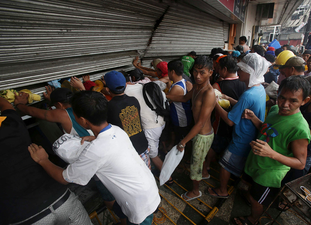 Description of . Residents push a shutter to open a small grocery to get food in Tacloban city, Leyte province central Philippines on Sunday, Nov. 10, 2013. The city remains littered with debris from damaged homes as many complain of a shortage of food, water and no electricity since the Typhoon Haiyan slammed into their province.  (AP Photo/Aaron Favila)