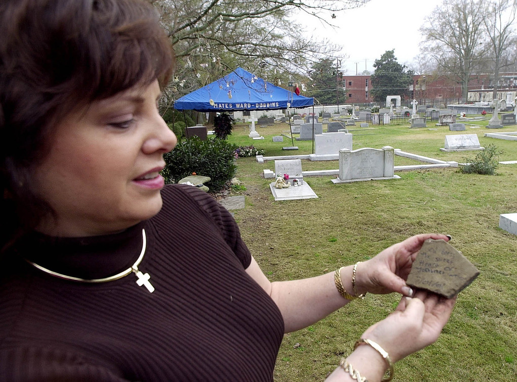 ". Patsy Ramsey holds a rock someone left at the grave of her daughter,  JonBenet Ramsey  at St. James Episcopal Church Cemetery in Marietta, Ga., Monday, Dec,. 17, 2001. On the rock the writing says ""God Bless the Sweet Heart of JonBenet Ramsey. 7/01/01.\""  Patsy Ramsey, along with a sister and friends of her family, were there to plant pansies and hang ornaments around the grave at rear with the items placed on it.(AP Photo/Atlanta Journal Constitution, Andy Sharp)"